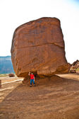 Monument Valley, child has fun by simulatings to carry a big roc — Stock Photo