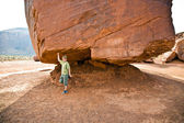 Monument Valley, child has fun by simulatings to carry a big rock — Stock Photo