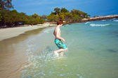 Young boy with red hair in swimsuit is running along the beautiful beach — Stock Photo