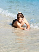 Boy has fun in the wonderful warm ocean and enjoys the water — Stock Photo