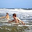 Boys enjoying the waves in the wild ocean — Stock Photo #5780129