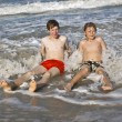 Brothers have fun at the beautiful neach of the ocean — Stock Photo