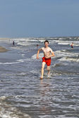 Boy running along the beautiful beach in the waves — Stock Photo