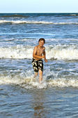 Young boy running through the water at the beach — Stock Photo