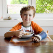 Boy at breakfast with cast on his broken arm — Stock Photo #5796642
