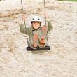 Boy on a swing is wearing a helmet and enjoys it - Stok fotoğraf