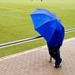 Man under umbrella is watching the football game — Stock Photo #5797079