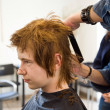 Smiling young boy with red hair at the hairdresser — Stock Photo #5797505