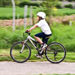 Young boy with helmet is riding mountain bike — Zdjęcie stockowe