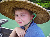 Boy wearing a hat out of palmtrees for sun protection — Stock Photo