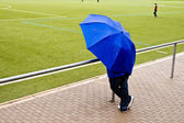 Man under umbrella is watching the football game — Stock Photo
