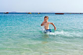 Boy has fun running in the water of the ocean — Stock Photo