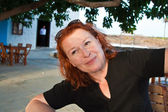Happy red hair women is sitting in an outdoor restaurant and smi — Stockfoto