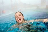 Girl has fun in the outdoor thermal pool in wintertime — Stock Photo