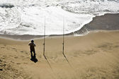 Angler at the beach with two rods — Stock Photo