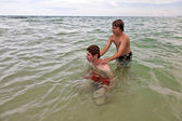 Boys having fun in the beautiful clear sea by playing pickaback — Stock Photo
