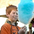 Boy enjoys cotton candy at the fair and licks his hands — Foto de Stock