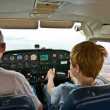Joung boy is flying aircraft assisted by a trainer — Stock Photo