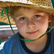 Child is wearing a hat made of bamboo during a boattrip — Stockfoto
