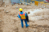 Building worker at the building site carrying an electrical cable — Stock Photo