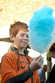 Boy enjoys cotton candy at the fair and licks his hands — Stock Photo