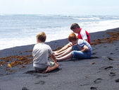 Family is collecting Gemstones on the vulcanic black beach in La — Stock Photo
