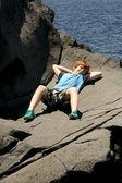 Menino feliz encontra-se sobre a rocha — Fotografia Stock