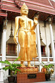 Standing Buddah in a temple in Bangkok is giving a handsign — Stock Photo