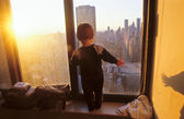 Young boy looks fascinated from the skyscraper to the streets of — Stock Photo