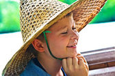 Child is wearing a hat made of bamboo during a boattrip — Stock Photo