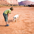 Monument Valley, boy strokes a beautiful lovely dog in the lands - Stock Photo