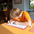 Boy doing homework for school at home — Stockfoto