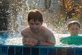 Kinderen spelen in een zwembad en een spottering met water — Stockfoto