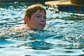 Boy with red hair is swimming in the pool and enjoys the fresh w — Stock Photo