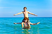 Brothers are enjoying the clear warm water at the beautiful beach and playi — Stock Photo