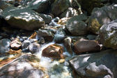 Colorful stones in the clear cold water of a creek with water from yosemite — Stock Photo