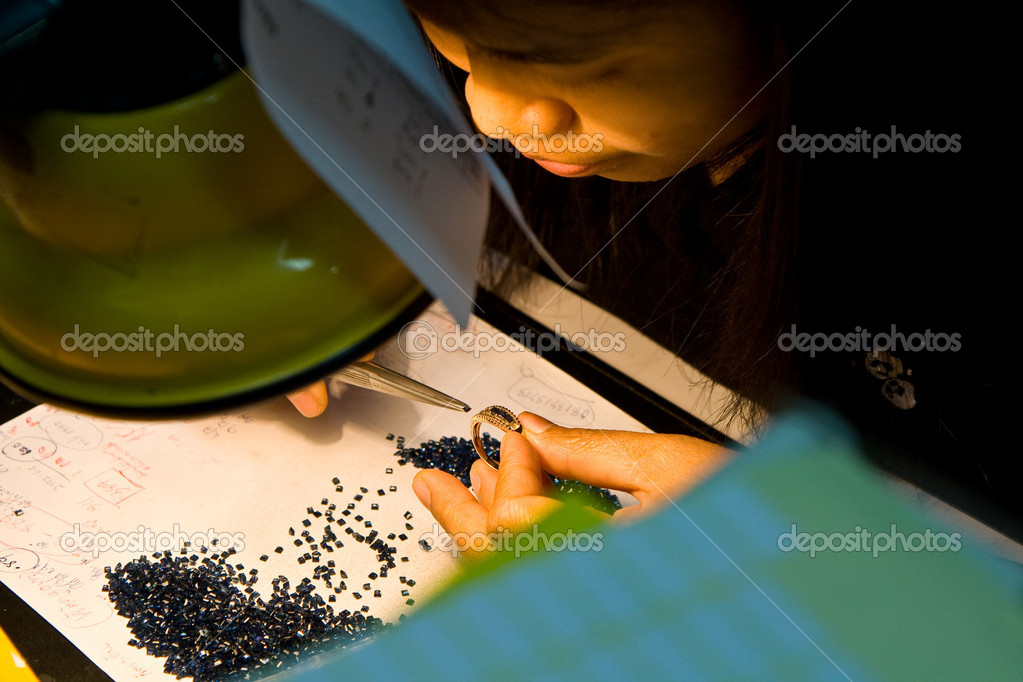 Female asian goldsmith puts jewelry into the golden ring — Stock Photo #5841157