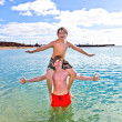 Stock Photo: Brothers playing pickaback in sea