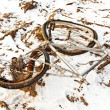 Littered and rusty bicycle as trash on snow - Stok fotoğraf