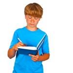 Cute boy writing in a book — Stock Photo
