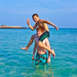 hermanos juegan juntos en un mar de aguas cristalinas un — Foto de Stock
