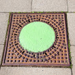A manhole cover in the street to enter the canalisation - Stok fotoğraf