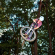 Cute teen jumping with his bike over a natural ramp in the fores — Stock Photo