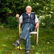 Portrait of elderly man sitting happy in his garden — Stock Photo