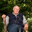 Portrait of elderly man sitting happy in his garden with closed — Stock Photo