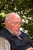 老人坐在一把椅子在他的花园和看起来 thinkful — 图库照片