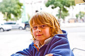 Boy with long hair and brown eyes is looking very self confident and happy — Stock Photo