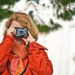 Nice lady with red hair, tourist,  takes pictures of a historic - Stock Photo