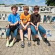 Three friends relaxing and sitting on a concrete bench at the skate park — Stock Photo