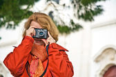 Nice lady with red hair, tourist, takes pictures of a historic — Foto Stock